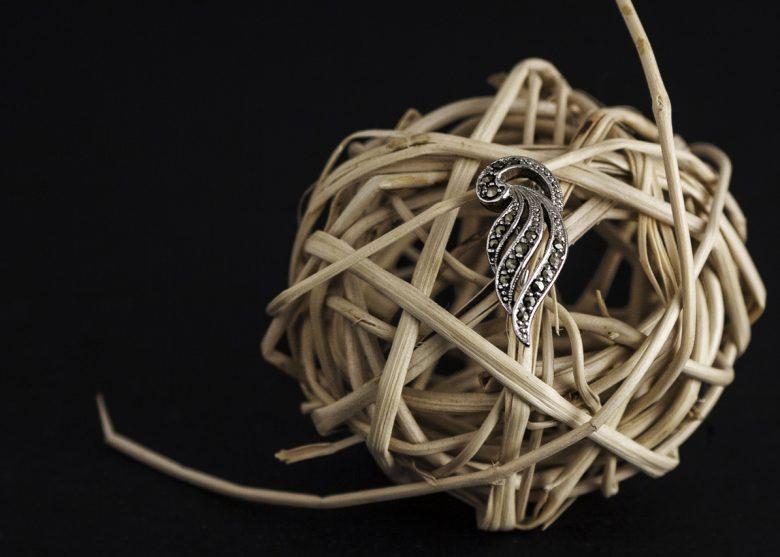 Photographie d'un broche en métal sur une boule de rotin.