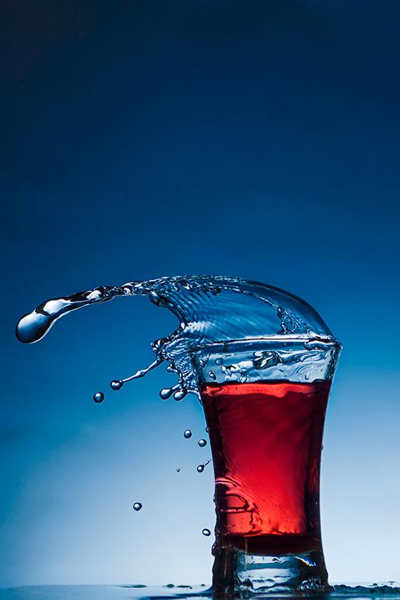 Verre rempli de colorant alimentaire et éclaboussures d'eau.