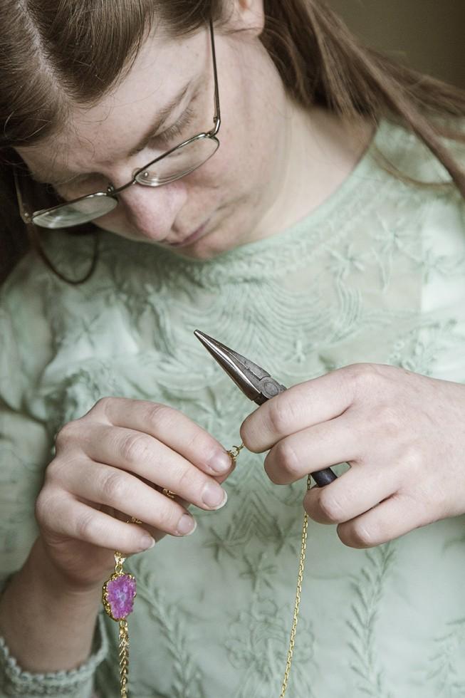 Fanny concentrée lors de l'assemblage d'un collier.