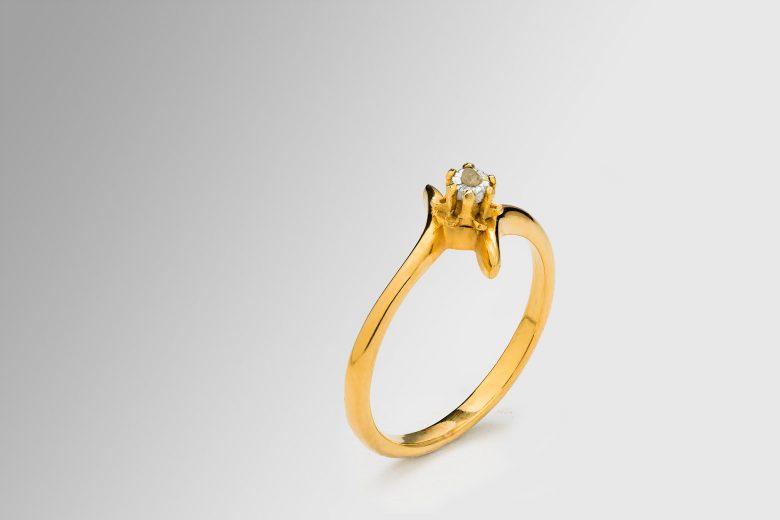 Bague en or avec diamant non-taillé photographié sur un fond en dégradé du gris léger au blanc.