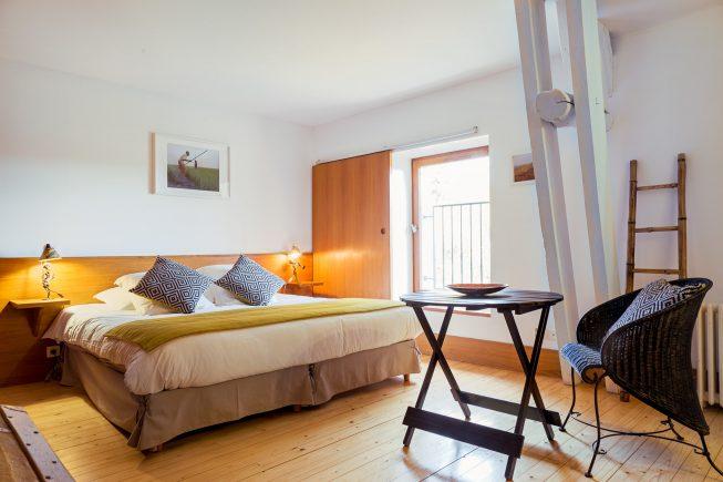 Domaine de La Reculée, photographie d'intérieur du gîte et des chambres d'hôtes. Vue d'ambiance de la chambre djoliba aux accent maliens et au ton jaune. Cette chambre est située à l'étage.