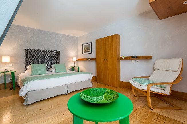 Domaine de La Reculée, photographie d'intérieur du gîte et des chambres d'hôtes. Vue d'ambiance de la chambre d'hôte pangalanes habillée de vert dans une ambiance rappelant l'île de Madagascar. Cette chambre est située à l'étage