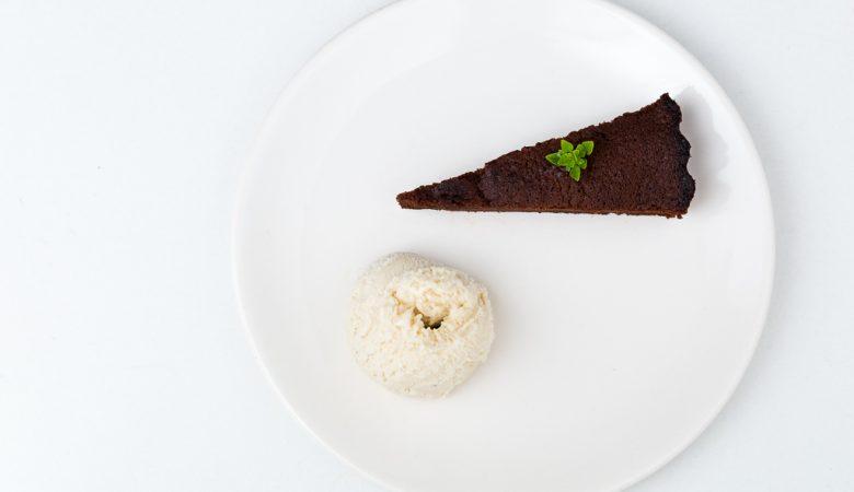 Photographie épuré d'une part de gâteau à la courgette et au chocolat accompagné d'une boule de glace.